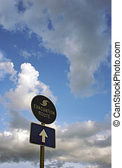 blue and white hurricane evacuation route signs against a cloudy sky