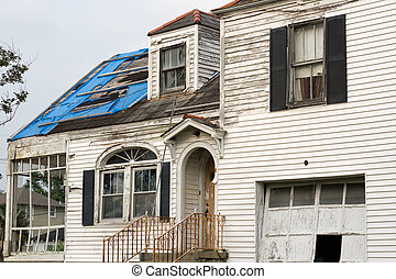 nearly two years post-Katrina, abandoned houses are found throughout New Orleans - this one still has the tattered remains of a FEMA blue roof and some of the vinyl siding that wasn't blown away