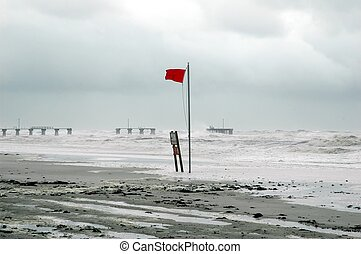 Hurricane. Red warning flag with damaged pier in background....