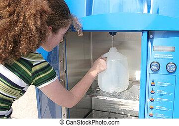 Hurricane Supplies - A teen girl filling a water bottle at a...