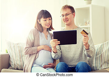 husband and pregnant wife shopping online at home