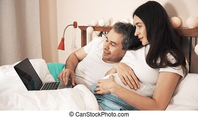 Husband and pregnant wife using their laptop in the bed