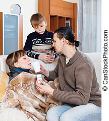 husband and son caring for sick woman