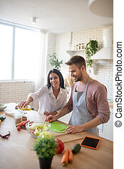 Husband and wife adding olive oil to vegetable salad