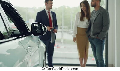 Husband and wife are choosing their first car together and talking to confident salesperson in motor show, happy woman is smiling and listening. Focus on shiny automobile.
