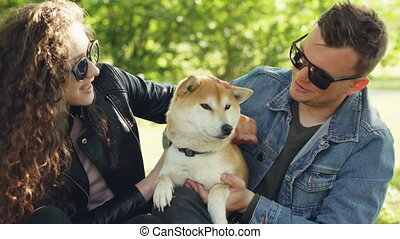 Husband and wife are kissing their favourite pet cute dog...