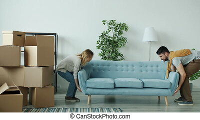 Husband and wife are carrying couch to new apartment then sitting and relaxing feeling exhausted after hard work. Family life and relocation concept.
