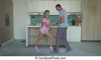 Husband and wife dancing together at home