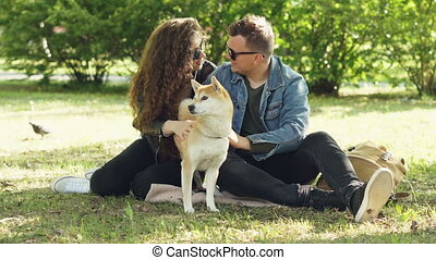 Husband and wife happy couple are fussing their pet shiba...