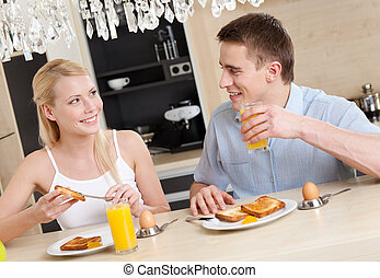 Husband and wife have a snack in the kitchen