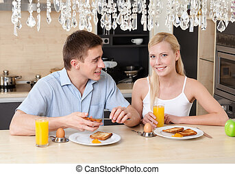 Husband and wife have breakfast in the kitchen