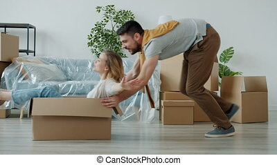 Husband and wife are having fun riding cardboard boxes enjoying relocation to new apartment together. Happiness and modern youth lifestyle concept.