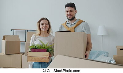 Husband and wife young people are holding belongings in boxes smiling looking at camera during relocation to new house. Family and housing concept.