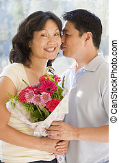 Husband and wife holding flowers kissing and smiling