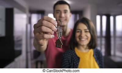 Husband and wife holding keys to new home