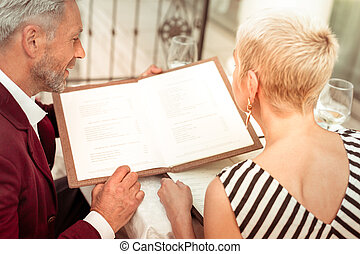 Husband and wife reading the menu having romantic evening date