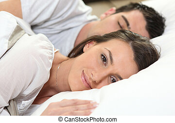 Husband and wife sleeping in their bed