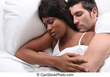 Husband and wife snuggling in bed
