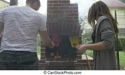Husband and wife taking care of the burning wood in grill...