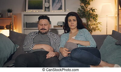 Husband and wife watching drama on TV with sad faces sitting...