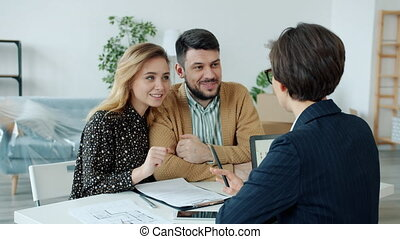 Husband and wife young people discussing real estate deal with agent reading contract at table