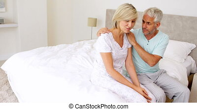 Husband comforting his wife sitting on bed