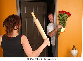Husband coming home late to an angry wife who is holding a rolling pin