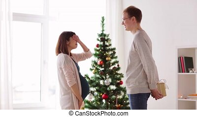 husband giving christmas present to pregnant wife