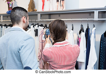 husband helping wife to choose clothes