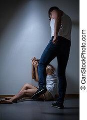 Husband kicking his wife