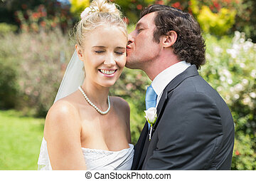 Husband kissing his new wife on the cheek