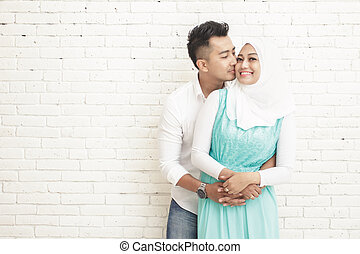 husband kissing his wife while hugging from behind