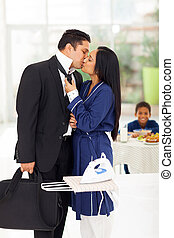 husband kissing wife before going to work