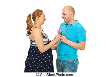 Husband offer pink rose to pregnant wife