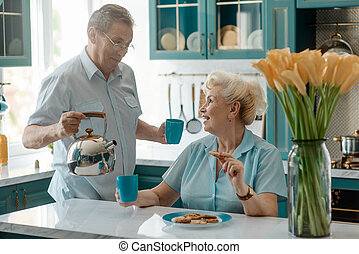 Husband pouring tea for wife, taking care of her, while she eats cookies