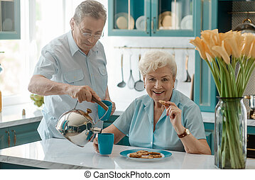 Husband pouring tea into wife's cup, taking care of her