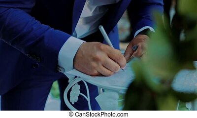 Husband puts his signature on the wedding ceremony