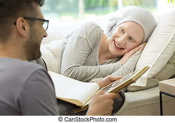 Husband reading book to smiling sick woman with headscarf