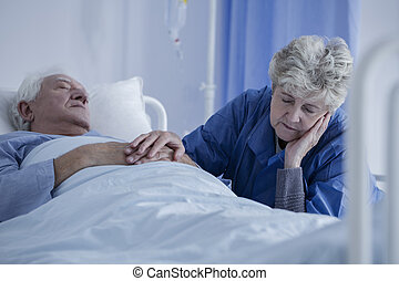 Tired senior woman sitting by her unconscious husband who is recovering from a serious surgery
