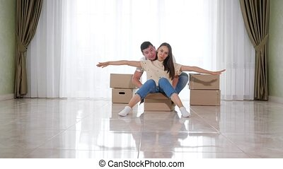 husband rides smiling wife in big box on white floor