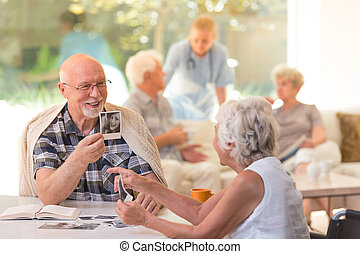Husband showing photos - Husband in glasses sitting by the...