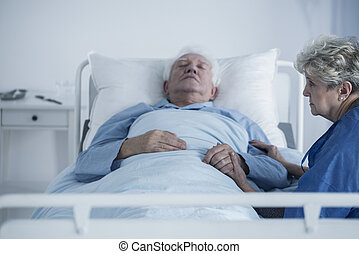Caring wife holding husband's hand who is suffering from cancer in the hospital