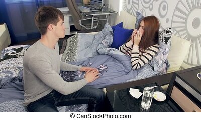 Husband takes care of sick wife with fever in bed