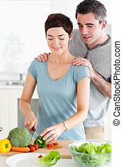 Husband watching his wife cutting vegetables