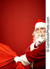 Hush - Portrait of Santa Claus with huge red sack keeping...