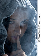 Hush!Hidden woman in smoke - Head of young woman with hood ...