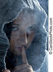 Hush!Hidden woman in smoke - Head of young woman with hood...