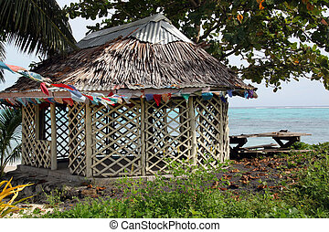 Hut with flags under tree on the beach in Savaii island, ...
