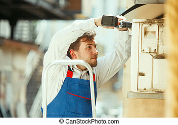 HVAC technician working on a capacitor part for condensing unit. Male worker or repairman in uniform repairing and adjusting conditioning system, diagnosting and looking for technical issues.