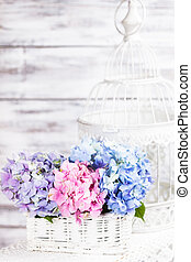 Hydrangea flowers in the white basket. Flower decor for the...